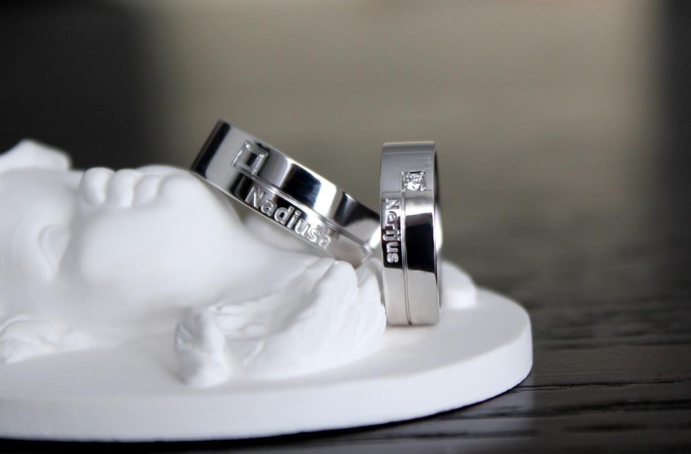 Balto aukso, rodžiuoti vestuviniai žiedai su deimantu. Graviruotas paviršius.