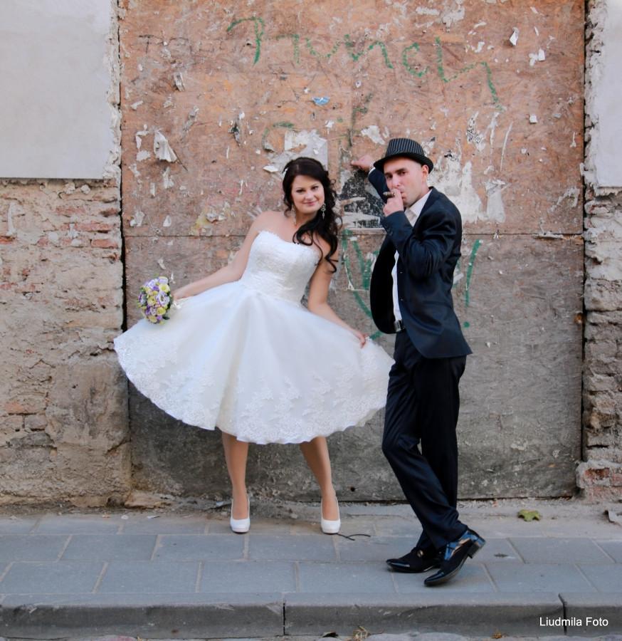 Zaisminga,pieno baltumo,iki blauzdų ilgio,pūsta vestuvinė suknelė. Gorsėtas ir apačia puošta rankū darbo nėriniais.