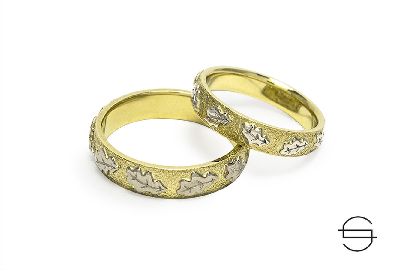 Geltono aukso vestuviniai žiedai su ąžuolo lapeliais.