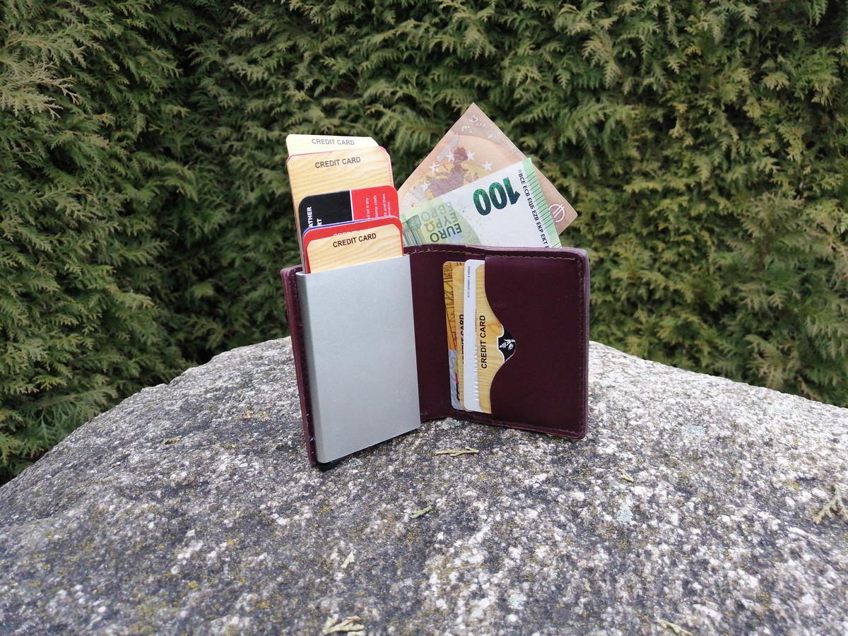 Natūralios odos minimalistinė  piniginė su įspaudu ir įmontuotu automatiniu dėkliuku kortelėms  Išdėstymas-vienas skyrelis popieriniams pinigams,  metalinis dėkliukas ,į kurį telpa 6-10 korteliu   du