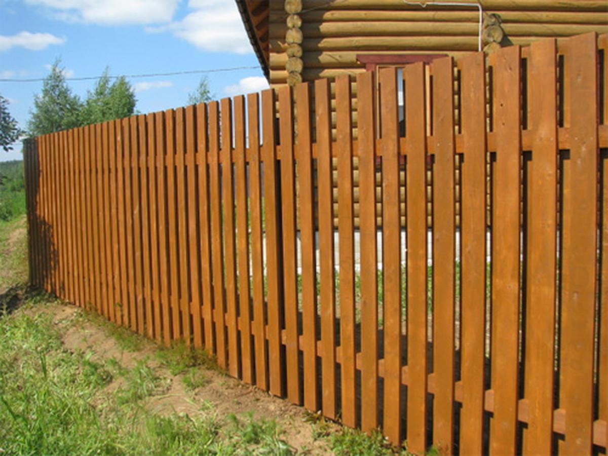 Medinės tvoros su metaliniais stulpais.