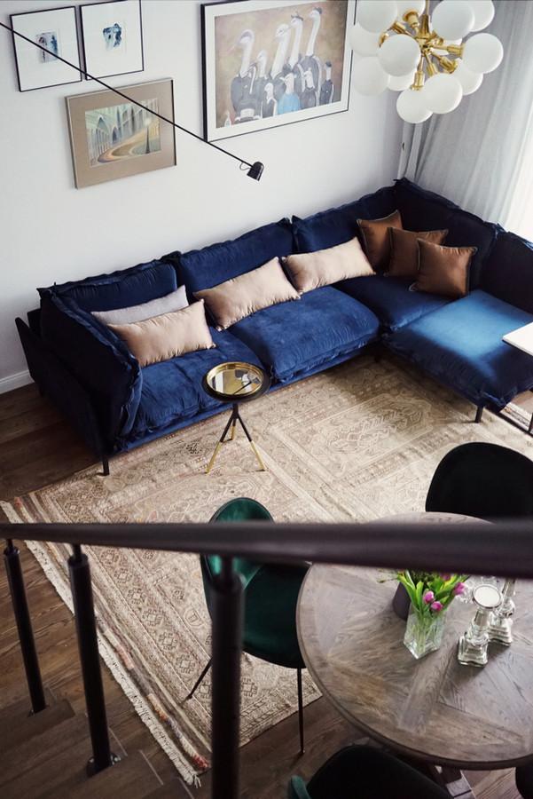 Patogi mėlyno aksomo sofa svetainėje puikiai dera su patrintu kilimu ir 1970 metų šviestuvu, kuriuos radome vienoje antique parduotuvėleje.
