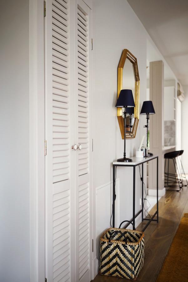 Prieškambario interjero freagmentas. Moderni konsolė su marmuriniu stalviršiu ir antikvarinis veidrodis.