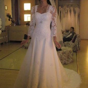 Prabangi, ilga vestuvinė suknelė su šleifu. Suknelė puošta nėriniais. Ant pečių, nuimamas švarkelis-bolero su ilgomis rankovėmis.