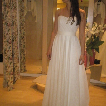 Ilga, vestuvinė suknelė. Viršus puoštas švelnia drapiruote. Apačia, platus tiulinis sijonas.