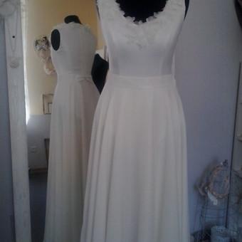 Ilga, vestuvine suknele,dveju daliu: bodis puostas lengvomis gelytemis ir ilgas,platus, keliu sluoksniu sijonas. Nugara puosia stilingas kaspinukas.