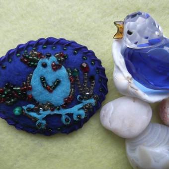 Sagė ''Mėlynas paukštelis'' Mėlynos spalvos veltinio pagrindas, siuvinėta įvairių spalvų biseriu ir karoliukais. Mėlyna sutažo apdailos juostelė. Dydis: 5x5,8 cm.