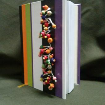 Knyga dekoruota mediniais karoliukais. Knyga gaminta rankomis : siutas blokas.