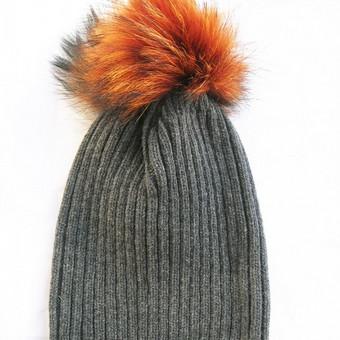 Stilinga minimalistinio dizaino kepurė su natūralaus kailio bumbulu. Universalus dydis tinka mažyliams, paaugliams ir mamytėms!  Patogu - bumbulas prisisega spaude, taigi skalbiant bumbulą galima nuimti. Kepurės mezgimo raštas, kaip pagrindinėje nuotraukoje.  Kepurės mezgamos iš ėriukų arba merino vilnos. 2014/2015 metų kolekcijoje dizainerės ypatingą dėmesį skyrė bumbulams, kurie šį sezoną yra ypač spalvingi. Bumbulai gaminami remiantis sąžiningos prekybos ir gamybos principais iš laukinių gyvūnų, kaip usūriniai šunys ar lapės arba iš Bolivijos alpakų kailio auginamų mažuose kaimeliuose.  Medžiagos sudėtis: kepurė - 80% vilna/20% poliamidas, bumbulas - natūralus kailis  Spalva: kepurė - tamsiai pilka, bumbulas - oranžinė  Kolekcija ruduo/žiema 2014-2015. Pagaminta Danijoje, prekės ženklas HUTTEliHUT®.
