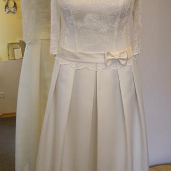 Korsetinė suknelė su klostuotu atlasiniu sijonu. Viršus puoštas nėriniu.