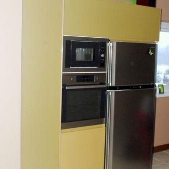 Virtuvės baldas su blizgiais aukso spalvos dažyto stiklo  fasadais, aliuminio profilio rėmeliu ir rankenėlėmis. Blum furnitūra.