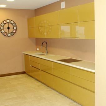Virtuvės baldas su blizgiais aukso spalvos  fasadais ir rankenėlėmis. Blum furnitūra.
