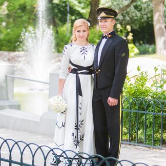 Ypatinga,ilga vestuvinė suknelė. Audinys-šilkas su linu pieno baltumo spalvos. Suknelė papuošta autorinė augalinių motyvų aplikacijomis juodos spalvos. Kompozicija papildo stilingas dirzas.