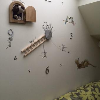 Laikrodis su pelytėm mergaičių kambaryje. Piešta ant sienos.