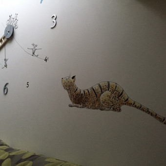 Piešinys ant sienos. Laikrodis. Katinas