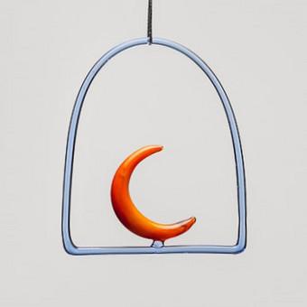 """Šis mažas pakabinamas mėnulis atlieka vitražiuko(šviesos gaudytojo) funkciją. Kabinamas ant lango, sienos, po šviestuvu. Oranžinio ar geltono stiklo """"Mėnulis"""" Dydis 10x10cm"""
