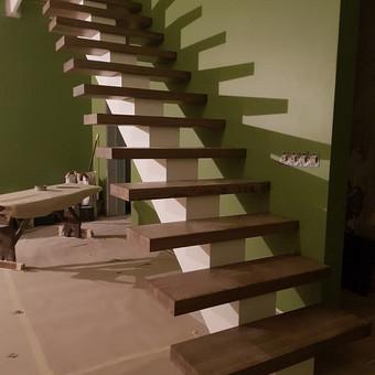 Metalinis laiptų karkasas su 6cm storio uosio pakopomis. Karkasas dažytas baltais matiniais metalo dažais. Pakopos padengtos beicu ir poliuretaniniu laku