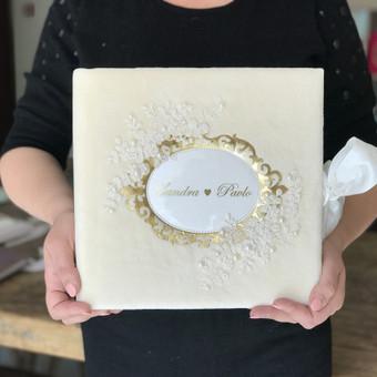 Klasikinis vestuvių nuotraukų albumas, šampaniniu aksomo viršeliu, aukso ornamentu, dekoruotas nėriniais.