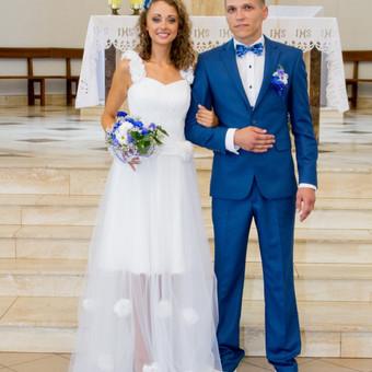 Dviejų dalių vestuvinė suknelė. Trumputė suknelė su draperija ir saulės kliošo sijonuku. Petnešos puoštos neapdorotomis gėlėmis, kad būtų panašu į plunksnas.