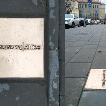 Reklaminė ploktšelė, įmontuota grindinyje, Vilnius. Matmenys 37x37 cm, bronza.