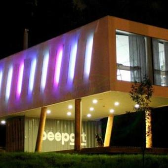 Neįprastas pastatas Pilaitėje: juriniai konteineriai, apšiltinti šiaudais, apželdintas stogas. RGB LED fasado apšvietimas po tentu. Atrodo kosmiškai.