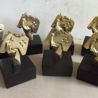 Lietuvos žaidimų kūrėjų asociacijos apdovanojimų nominacijų statulėlės, pagamintos pagal pateiktą modelį. Žalvaris, ąžuolas, h - 15 cm