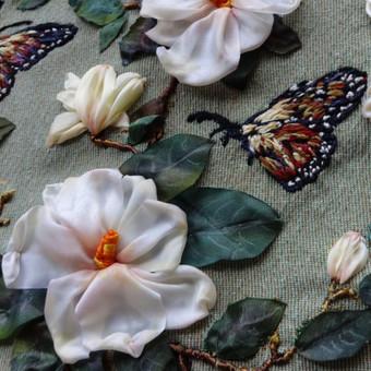 Magnolija ir drugeliai. Ranku siuvinejimas juostelemis ant sieninio gobeleno paveikslo Tikslus siuvinėjimo ir jo tonavimo pakartojimas yra neįmanomas, kiekvienas išsiuvinėtas paveikslas yra vienintelis.