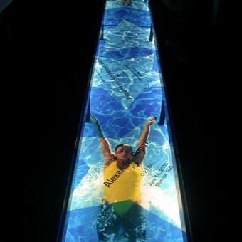 Skaitmeninė spauda ant plėvelės, įklijuota i tarpą grindyse ir uždengta stiklu, suimituojant baseiną.
