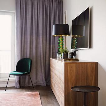 Miegamojo komoda pagaminta iš riešuto lukšto puikiai dera su žaliais elementais.