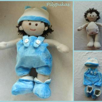 Lėlė kūdikis. Dydis apie 25 cm, pagamintas iš medvilnės. Rūbeliai nusiima, rankytės ir kojytės juda.