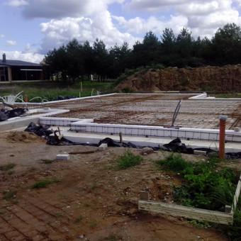Plokštuminių pamatų įrengimas .Nuimtas augalinis sluoksnis , išvedžiotas drenažas ir lietaus kanalizacija,patiesta geotekstilė ,supilta skalda , žvyras ,sutankintas pagrindas išvedžiota ka ...