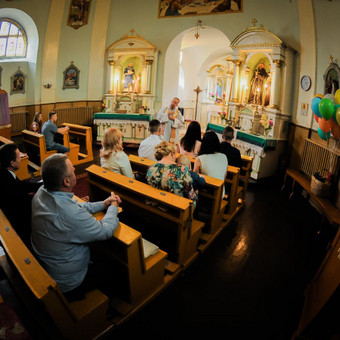 Krikštynų metu, bažnyčios patalpa yra labai maža, naudojamas plataus kampo objektyvas.