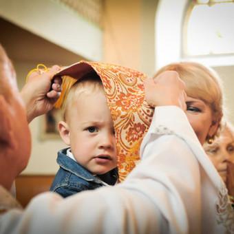 Krikštynų akimirka bažnyčioje, dažnai vaikai kunigo bijo, ir tai dažnai matosi kadruose.